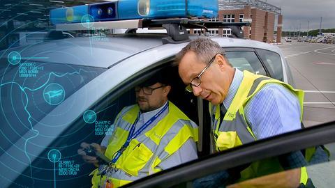 Zwie Protagonisten mit Warnwesten unterhalten sich. Einer sitzt im Fahrzeug und sein Kollege beugt sich bei geöffneter Fahrertür zu ihm hinunter.