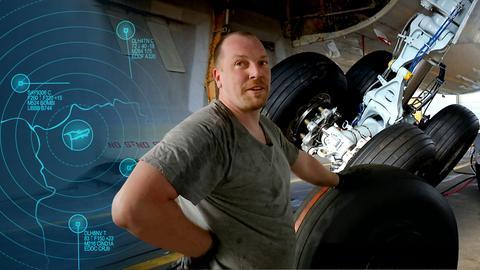 Mittendrin-Protagonist im Vordergrund. Im Hintergrund ist das Fahrwerk einer Boeing 767 zu sehen.