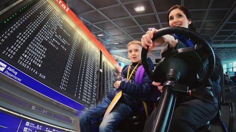 Eine Frau und ein Kind fahren durch den Flughafen.