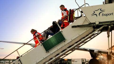 Sanitäter transportieren über eine Treppe einen Patienten aus einem Flugzeug