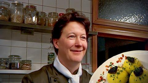 Frau in Küche und Teller mit Knödeln