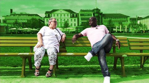 Coach Kelechi sitzt mit Altenpflegerin Christine auf einer Bank.