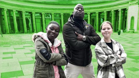 Motivations- und Bewegungscoach Kelechi steht neben zwei Mädchen.