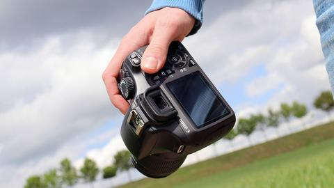Nahaufnahme einer männlichen Hand, die einen Fotoapparat hält. Unscharf im Hintergrund sind Bäume und Wiese zu sehen.