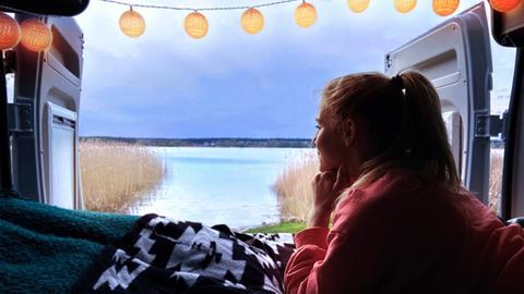 hr-Reporterin Maike Tschorn blickt in der Abendsonne aus ihrem Campervan auf die Mecklenburgische Seenplatte.