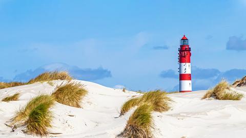 Ein Leuchtturm in den Dünen, im Hintergrund blauer Himmel