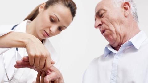 Eine ärztin untersucht einen älteren Herren an seiner Hand.