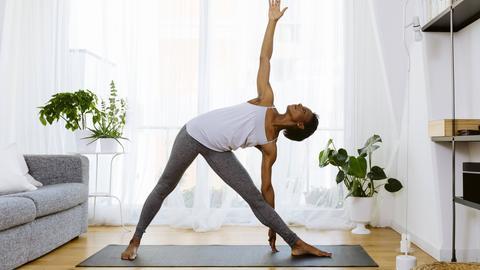 Eine Person macht eine Übung in ihrem Wohnzimmer.