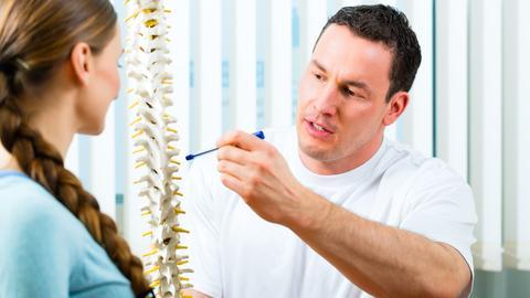 Ein Arzt erklärt an einem Wirbelsäulenmodell die Funktionen im Rücken