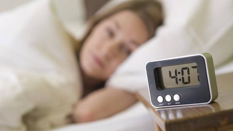 Frau liegt mit offenen Augen im Bett und schaut auf die Uhr. Sie hat Schlafstörungen.