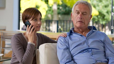 Ein Mann hat einen Schlaganfall, seine linke Gesichtshälfte hängt leicht herab. Eine Frau ruft den Rettungsdienst.