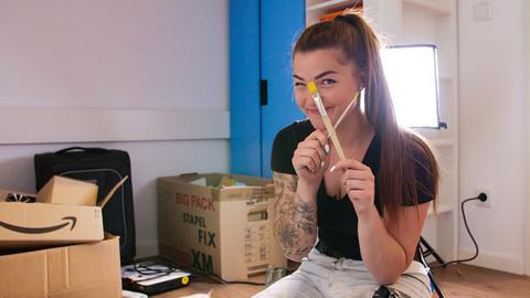 Lisa Manns, eine der jüngsten Maler- und Lackierermeisterinnen in Deutschland, mit gekreuzten Pinseln