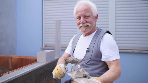 Protagonist mit Mauerspachtel und Mörtel in der Hand vor einer halbfertigen Mauer.