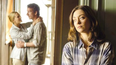 Junge Frau lehnt an einem Türrahmen und blickt nach links, im Hintergrund ein Paar.