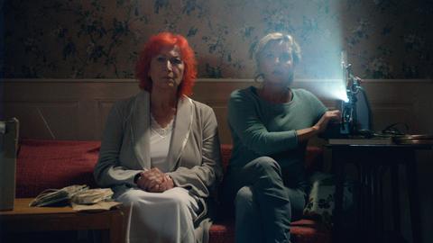 Zwei Frauen sitzen nebeneinander auf dem Sofa.