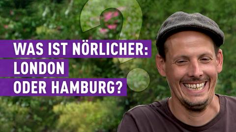 Protagonist sitzt lachend vor einer grünen Hecke.