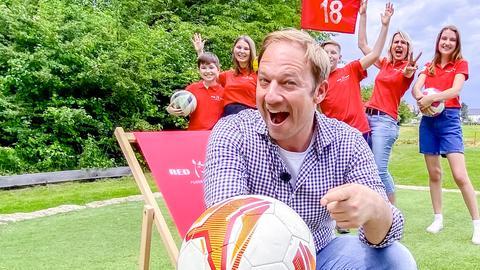 Moderator Tobi Kämmerer sitzt in einem Klapptstuhl und hat einen Fußball in der Hand. Hinter ihm stehen junge Menschen auf dem Fußballgolfplatz und jubeln.