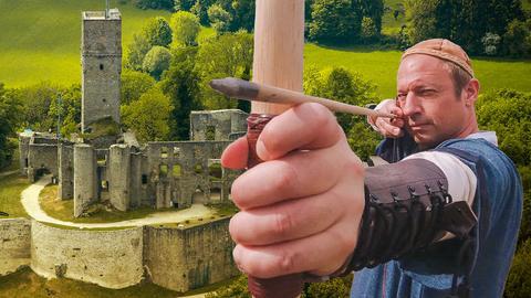 Tobi Kämmerer schießt konzentriert mit Pfeil und Bogen. Im Hintergrund zu sehen die Burg Königstein.