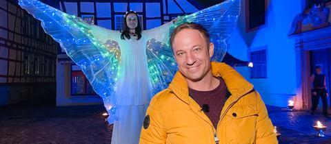 """Tobi Kämmerer abends in Erbach. Ein leuchtender """"Engel"""" im Hintergrund."""