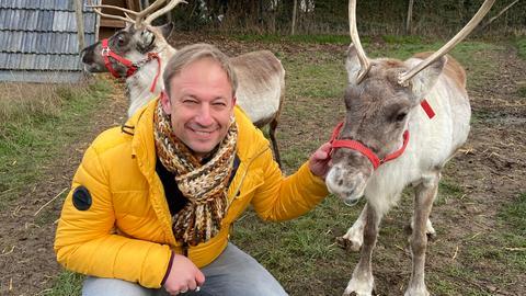 Moderator Tobi Kämmerer posiert mit einem Rentier namens Momo.