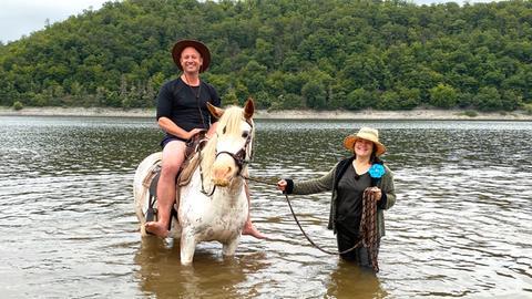 Tobi Kämmerer sitzt auf einem Pony, geführt von Priscilla Wilhelmi – mitten im Edersee.