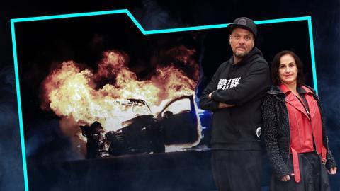 Heike Borufka und Basti Red stehen Rücken an Rücken. Neben ihnen ein brennendes Auto und Polizeilichter im Hintergrund.