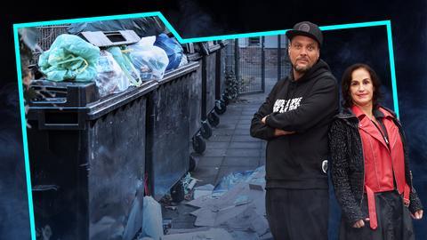 Heike Borufka und Basti Red stehen Rücken an Rücken. Neben ihnen eine Reihe voller Müllcontainer in einem Hinterhof.