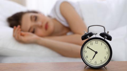Ein Wecker zeigt kurz vor sieben, dahinter schläft eine Frau im Bett