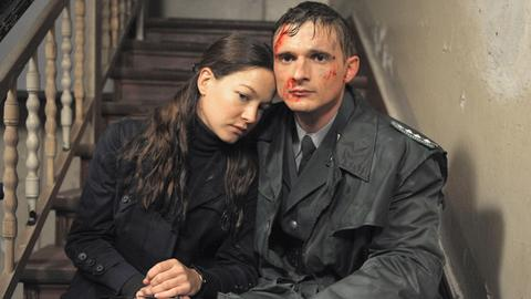 Martin sitzt blutend neben Julia auf einer Treppe.