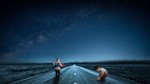 Zwei Kinder spielen auf einer Straße ohne Autos unter Sternenhimmel