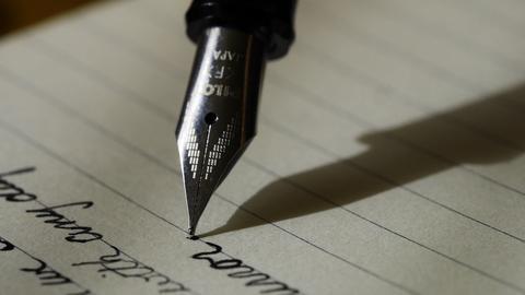 Ein Tintenfüller in Nahaufnahme über einem beschriebenen Blatt Papier.