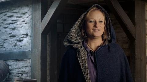Eine Frau in einem mittelalterlichen Kapuzenumhang.