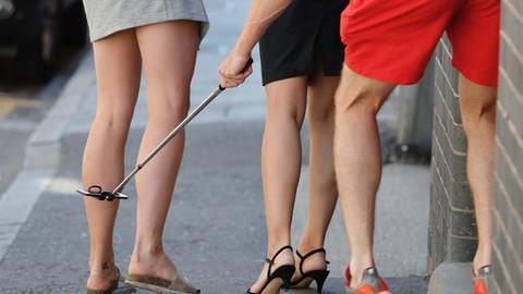 Ein junger Mann fotografiert mit seinem Smartphone auf der Straße zwei jungen Frauen unter ihre Kleider.