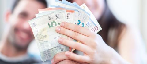 Eine Frau und ein Mann halten gemeinsam mehrere Euroscheine in den Händen.