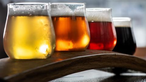 Verschiedene frisch gezapfte Sorten Craft Beer (l-r: Summer Ale Colonia, Indian Pale Ale Progusta, Brown Ale The Brale und Schwarzbier Darkon) auf einem länglichen Holztablett.