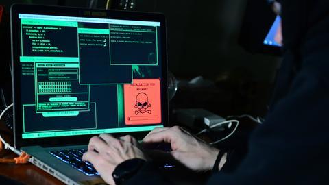 Ein dunkel gekleideter Mann sitzt in einem abgedunkelten Raum vor einem Laptop, auf dem unter anderen ein Totenkopf zu sehen ist.