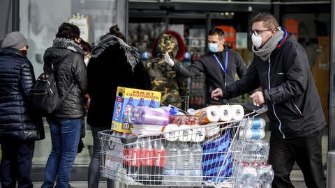 Menschen tragen Atemschutzmasken und stehen vor einem Supermarkt in einer Schlange.
