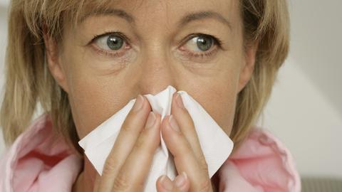 Eine ältere Frau putzt sich die Nase und schaut besorgt.