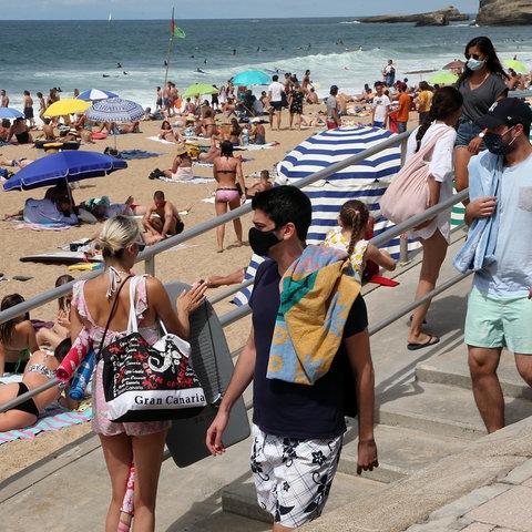 Strandbesucher halten sich mit Mund-Nasen-Bedeckung am Strand von Biarritz, Frankreich, auf.