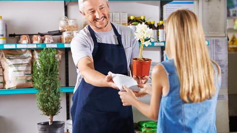 Ein Verkäufer im Baumarkt überreicht einer Kundin eine Orchidee im Topf und eine kleine Packung Pflanzenerde.