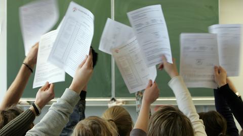 Schüler*innen halten vor der Tafel ihre Halbjahreszeugnisse nach oben in die Luft.