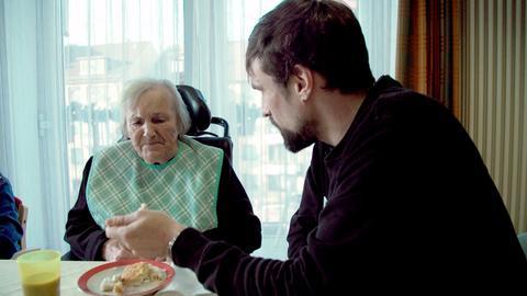 Reporter Martin Rieck (rechts) hilft Frau Gliwitzki beim Kuchen essen, da sie ihre Gabel nicht mehr alleine halten kann. Die Pfleger achten darauf, dass die Bewohner in ihrem Alltag nur so viel Hilfe wie nötig bekommen.