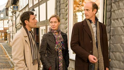 Rudolf (Johannes Herrschmann, re.) und Karina (Katja Weitzenböck) zeigen Klaus (Heikko Deutschmann) die Uhrmacherwerkstatt.