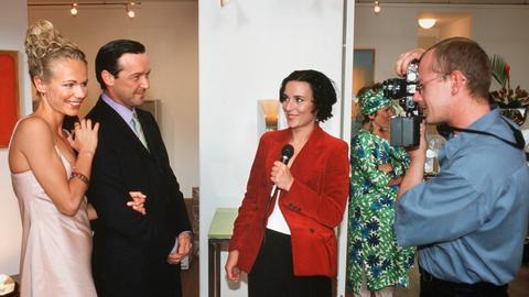 Die erfolgreiche Stilberaterin Juliane (Claudine Wilde, li.) eröffnet zusammen mit ihrem Freund, dem Galerist René (Michael Roll, 2. v. li.) eine Kunstausstellung, die von der Presse positiv aufgenommen wird.