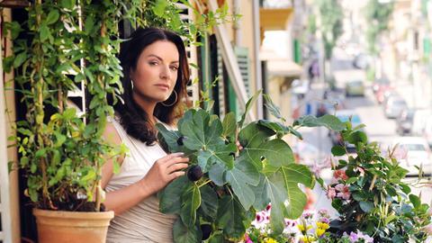 Bella Sommer (Christine Neubauer) versorgt in ihrer Wohnung in Palma ihre Balkonpflanzen.