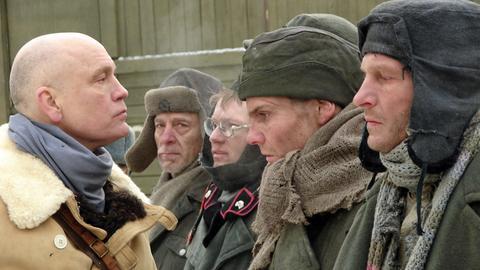 Oberst Pavlov (John Malkovich, li.) nimmt die deutschen Kriegsgefangenen ins Visier, darunter Max (Thomas Kretschmann, re.) und Klaus (Daniel Brühl, 2. v. re.).