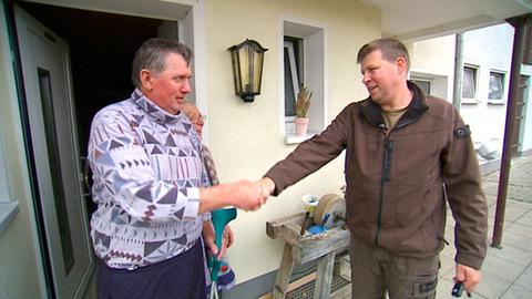 Betriebshelfer Martin Rotzoll (rechts) verabschiedet sich von Hanna und Bernhard Brahm, deren Hof er für einige Zeit übernommen hatte.