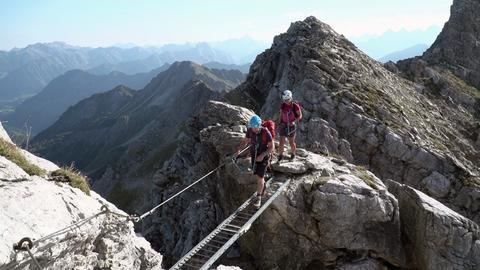 Bergsteiger an der Querleiter am Mindelheimer Klettersteig.