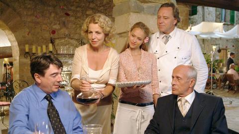 Walter Lenz (Gerd Silberbauer, re. hinten) bewirtet mit Gattin Hanna (Michaela May 2.vl.) und Tochter Lili (Ganeshi Becks) den zwielichtigen Manolo (Bernhard Leute, li.) und den schlitzohrigen Bankdirektor Kalterer (Heinz Trixner, re).