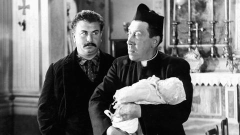 Don Camillo (Fernandel, r) weigert sich, das Baby seines Lieblingsfeindes Peppone (Gino Cervi) zu taufen.